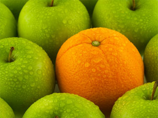 A photo of green apples and an orange