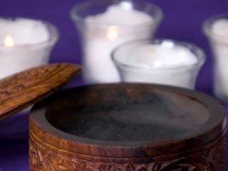 A photo of a ashes in container with candles behind