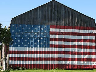 A photo of a barn with the US flag painted the walls
