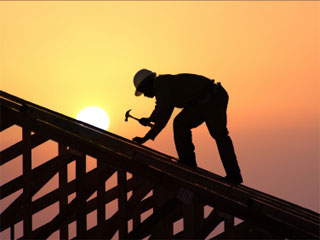A photo of a builder on a roof silloueted behind a bright sun