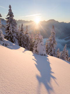 A photo of the sun rising over a snowy mountain scene