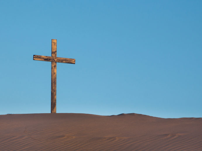 A photo of a wooden cross in the sand against a vivid blue sky