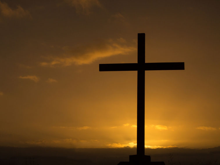 A photo of a cross against a sunset sky