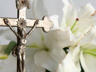 A photo of a crucifix next to a white lilies