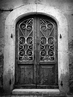 A black and white photo of an old wooden door