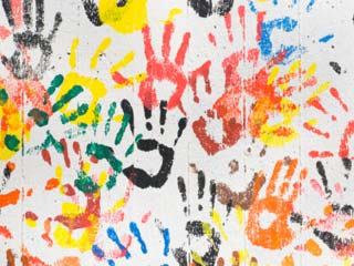 A photo of a many colored hand prints on a white background