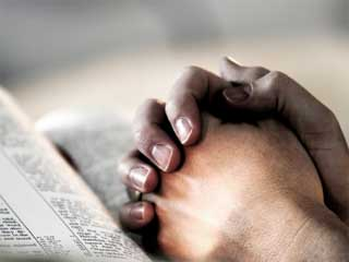 A photo of a man's hands clasped over a bible