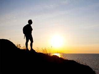 A photo of a hiker silhouetted against a sunrise