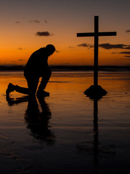 A photo of a man praying in front of a cross at sunset