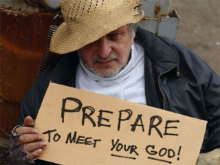 A photo of a man holding a sign that reads Prepare To Meet Your God!