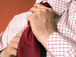 A photo of man adjusting his tie