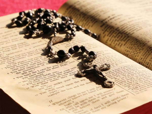 A photo of a Rosary on a bible.