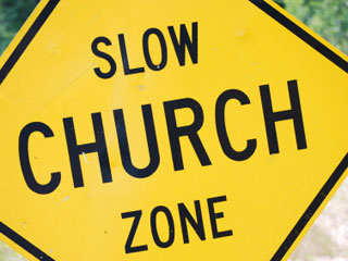 A photo of road sign that reads Slow Church Zone