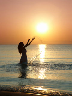 A photo of a woman in the water at sunset