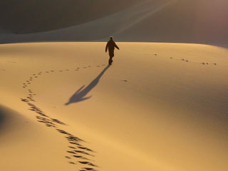 A photo of a single person walking alone in the desert
