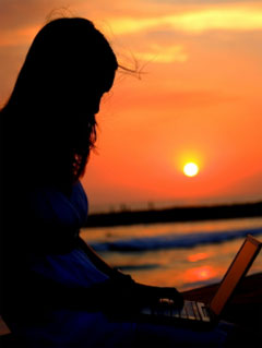 A photo of a woman sitting with a laptop in shadow against a sun set background