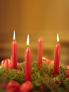A photo of an Advent Wreath with 3 lighted candles
