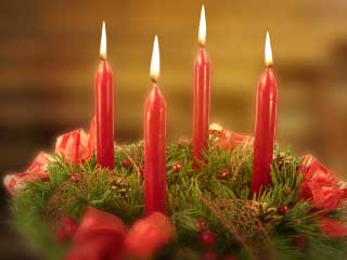 A photo of an Advent Wreath with 4 lighted candles
