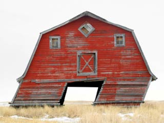 A photo of an old red barn leaning to the right