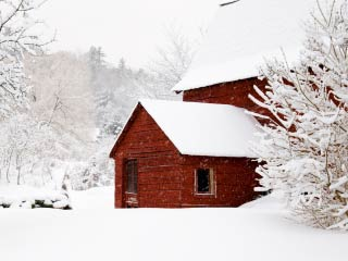 Photo of a red barn in a snow covered landscape