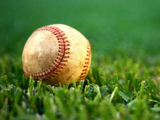 A photo of a baseball in the grass