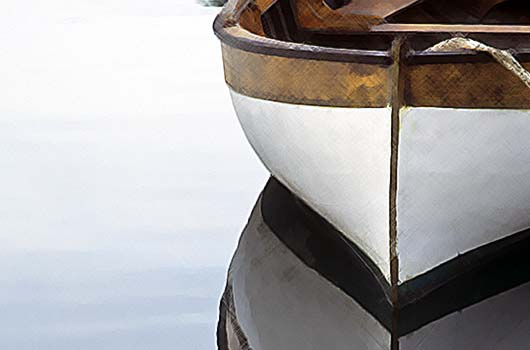 A photo of the front of a row boat with a vivid reflection in the water