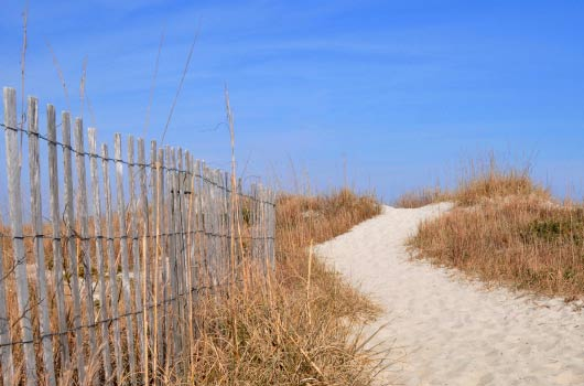 A photo of sandy beach scene with a weather worn fence