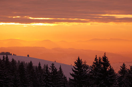 A photo of an orange sunrise looking out over a mountain landscape