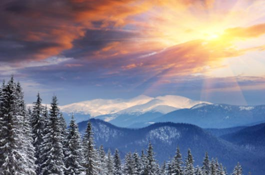 A photo of a bright sunrise over a snowy mountain range