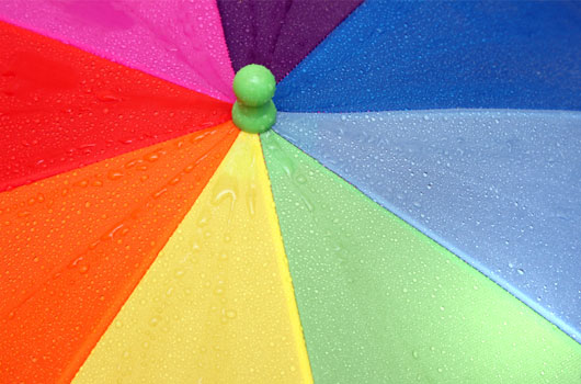 A photo a colorful umbrella covered with rain drops