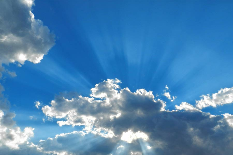A photo of a blue sky with clouds and sun rays