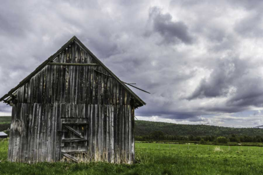 A photo of an old gray barn against a cloudy sky