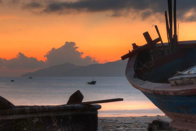 A photo of boats on a beach against a vibrant orange sunrise.