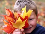 Photo of a smiling boy holding color Autumn leaves in front of a portion of his face