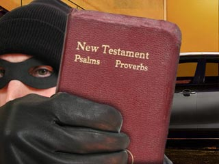 Photo of a burgler holding a small bible and standing infront of a car