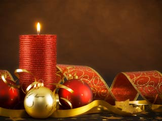 Photo of a red candle surrounded by gold bows