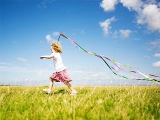 Photo of a child running through a field with a handful of long streamers blowing in the wind