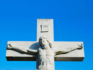 Photo of a stature of Christ against a bright blue sky