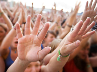 Photo of a crowd of people with their hands raised