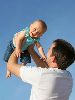 Photo of a father holding an small child over his head
