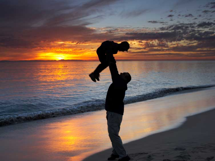 A photo of a father on the beach with his son