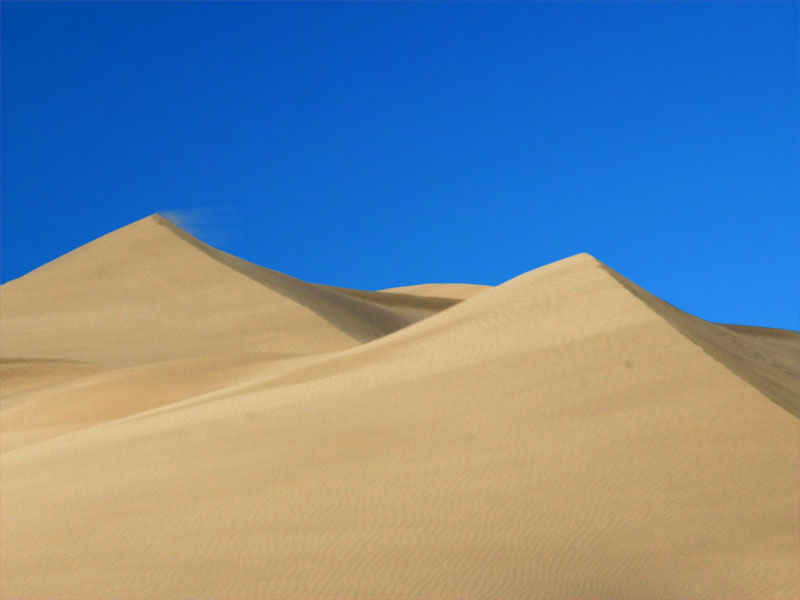 A photo of desert sand against a vivid blue sky