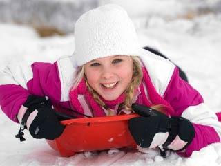 A photo of a girl on a snow sled