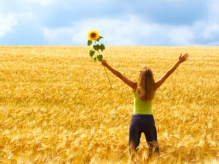 A photo of a woman holding a sunflower high while standing in a field of yellow wheat
