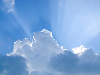 A photo of blue sky, puffy clouds and the sun's rays