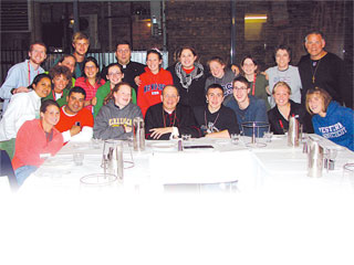 A photo of Bishop William Lori (center) and Msgr. Dariusz Zielonka (standing) joined World Youth Day pilgrims from the Diocese of Bridgeport for dinner in Sydney, Austrailia