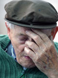 Photo of an elderly man looking down and depressed