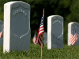 Photo of a tombstone and an American flag