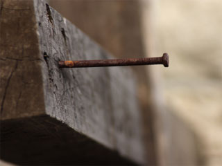 Photo of a rusty nail hammered part way into a wooden cross