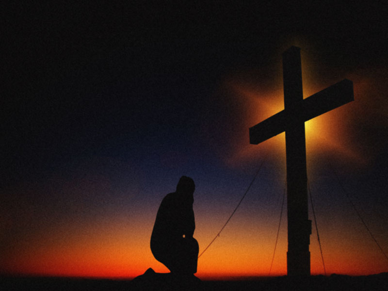 A photo of a man praying in front of a large cross.